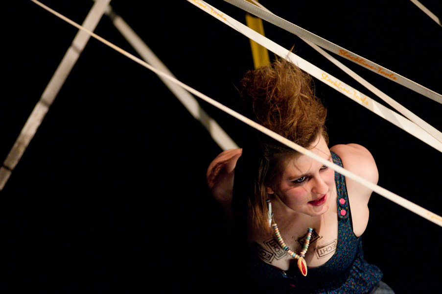 Actress performing in a web of slacklines during a theater production.